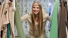 Mujer hermosa joven en la tienda de ropa Mujer rubia feliz entre los estantes de la ropa almacen de video