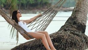 Mujer hermosa joven en las gafas de sol que se relajan en la hamaca en la playa tropical almacen de metraje de vídeo
