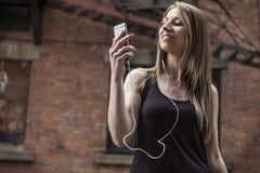 Mujer hermosa joven en música que escucha de la ciudad Imagenes de archivo