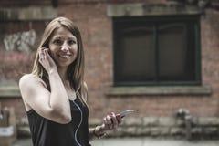 Mujer hermosa joven en música que escucha de la ciudad Fotos de archivo