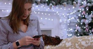 Mujer hermosa joven en mensajes de texto de la escritura de la noche de la Navidad del teléfono móvil, sentándose en el sofá en c almacen de metraje de vídeo