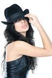 Mujer hermosa joven en sombrero negro sobre blanco Foto de archivo