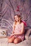 Mujer hermosa joven en traje del ángel con las alas rosadas Fotos de archivo
