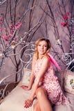 Mujer hermosa joven en traje del ángel con las alas rosadas Foto de archivo