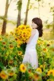 Mujer hermosa joven en un campo del girasol Fotografía de archivo