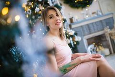 Mujer hermosa joven en un cuarto adornado para celebrar el Año Nuevo y la Navidad Imagen de archivo