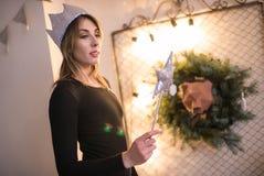 Mujer hermosa joven en un cuarto adornado para celebrar el Año Nuevo y la Navidad Fotos de archivo libres de regalías