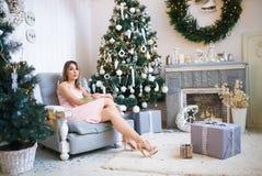 Mujer hermosa joven en un cuarto adornado para celebrar el Año Nuevo y la Navidad Fotos de archivo