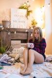 Mujer hermosa joven en un cuarto adornado para celebrar el Año Nuevo y la Navidad Fotografía de archivo