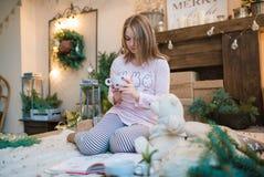 Mujer hermosa joven en un cuarto adornado para celebrar el Año Nuevo y la Navidad Imagen de archivo libre de regalías
