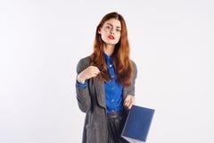 Mujer hermosa joven en un fondo ligero, preparación, cuaderno, profesor Imágenes de archivo libres de regalías