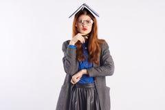 Mujer hermosa joven en un fondo ligero, preparación, cuaderno, profesor, vidrios Imagenes de archivo