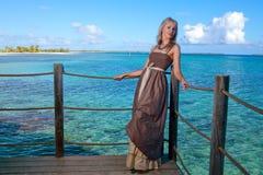 Mujer hermosa joven en un platform.portrait de madera contra el mar tropical Fotografía de archivo