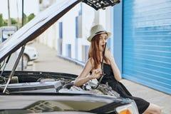 Mujer hermosa joven en un sombrero que repara un coche al aire libre en la ciudad, body shop Fotografía de archivo libre de regalías