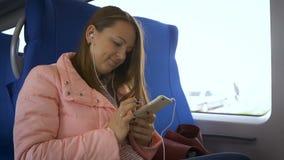 Mujer hermosa joven en un tren que escucha la música de su smartphone en los auriculares blancos metrajes