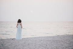 Mujer hermosa joven en un vestido blanco que camina en una playa vacía cerca del océano Imágenes de archivo libres de regalías
