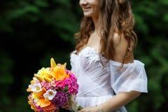 Mujer hermosa joven en un vestido blanco que presenta con un ramo Fotografía de archivo