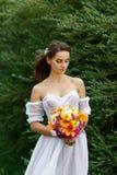 Mujer hermosa joven en un vestido blanco que presenta con un ramo Imagenes de archivo