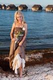Mujer hermosa joven en un vestido romántico con una rosa en la arena en el borde del mar Imagenes de archivo