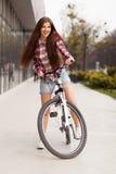 Mujer hermosa joven en una bicicleta Imagen de archivo libre de regalías