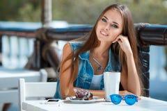Mujer hermosa joven en una tabla en café del verano Imagen de archivo