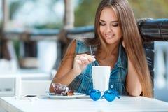 Mujer hermosa joven en una tabla en café del verano Imagenes de archivo