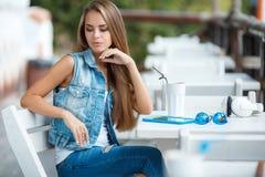 Mujer hermosa joven en una tabla en café del verano Foto de archivo libre de regalías