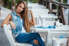Mujer hermosa joven en una tabla en café del verano Imagen de archivo libre de regalías