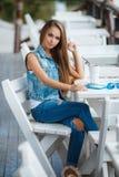 Mujer hermosa joven en una tabla en café del verano Fotografía de archivo libre de regalías