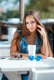 Mujer hermosa joven en una tabla en café del verano Imágenes de archivo libres de regalías