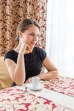 Mujer hermosa joven en vestido clásico negro con el pelo oscuro largo en un coffe de consumición del caffe por la mañana Fotos de archivo