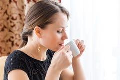 Mujer hermosa joven en vestido clásico negro con el pelo oscuro largo en un coffe de consumición del caffe por la mañana Foto de archivo libre de regalías