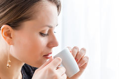 Mujer hermosa joven en vestido clásico negro con el pelo oscuro largo en un coffe de consumición del caffe por la mañana Imagenes de archivo