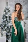 Mujer hermosa joven en vestido elegante verde en interior con el ch Fotografía de archivo libre de regalías