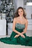 Mujer hermosa joven en vestido elegante verde en interior con el ch Imágenes de archivo libres de regalías