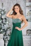 Mujer hermosa joven en vestido elegante verde en interior con el ch Foto de archivo libre de regalías