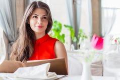 Mujer hermosa joven en vestido rojo en el restaurante Fotografía de archivo
