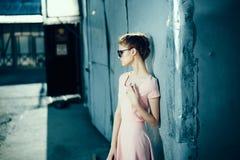 Mujer hermosa joven en vestido y gafas de sol rosados en la calle Foto de archivo libre de regalías