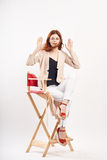Mujer hermosa joven en vidrios en un fondo blanco que se sienta en un taburete en el crecimiento completo, moda Imágenes de archivo libres de regalías