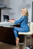 Mujer hermosa joven feliz con el ordenador portátil dentro Fotos de archivo