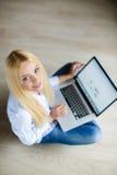 Mujer hermosa joven feliz con el ordenador portátil dentro Foto de archivo libre de regalías
