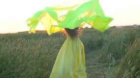 Mujer hermosa joven feliz en el vestido amarillo que corre en campo de trigo en el verano de la puesta del sol, concepto de la fe almacen de metraje de vídeo
