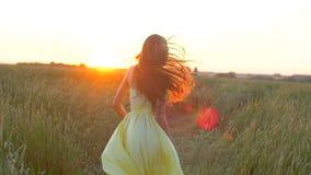 Mujer hermosa joven feliz en el vestido amarillo que corre en campo de trigo en el verano de la puesta del sol, concepto de la fe metrajes