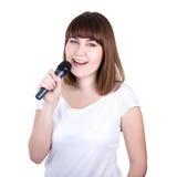 Mujer hermosa joven feliz que canta con el micrófono aislado encendido Fotos de archivo
