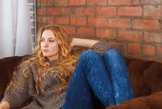 Mujer hermosa joven feliz que se relaja en el sofá en casa Fotografía de archivo