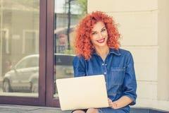Mujer hermosa joven feliz que usa el ordenador portátil fotografía de archivo libre de regalías