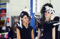 Mujer hermosa joven internacional de la perfumería de Intercharm XXI y de la exposición dos de los cosméticos en el vestido negro Fotos de archivo