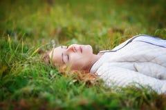 Mujer hermosa joven Muchacha de la belleza que miente en la hierba, ojos cerrados Foto de archivo libre de regalías