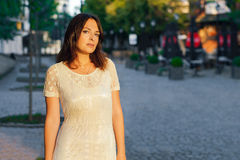 Mujer hermosa joven, oscuro-cabelluda, situación en la calle en el centro de ciudad en un día soleado, en un vestido blanco con l Imágenes de archivo libres de regalías