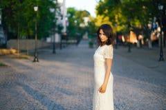 Mujer hermosa joven, oscuro-cabelludo, caminando abajo de la calle en el centro de ciudad en un día soleado, en un vestido blanco Fotografía de archivo